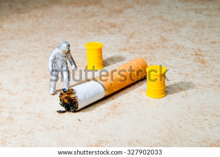 Small people investigating cigarette. The concept of health - stock photo