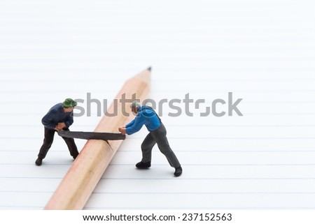 Small people with handsaw cutting the pencil on Blank page of note book  - stock photo