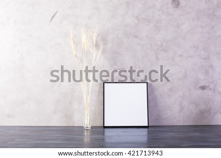 Small picture frame and wheat spikes on concrete background. Mock up - stock photo