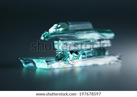 Small pieces of broken or shattered glass stacked,with dark background.  - stock photo