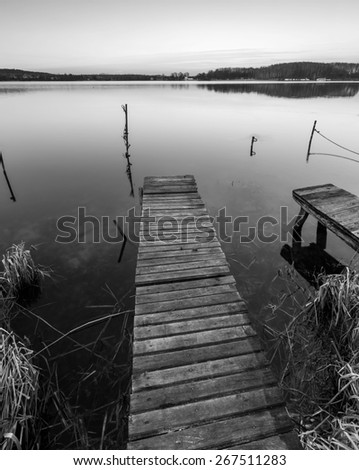 Small pier on lake, long exposure photo. Mazury lake district. Black and white photo. - stock photo