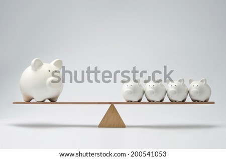 Small piggy banks and large piggy bank balancing on a seesaw - stock photo