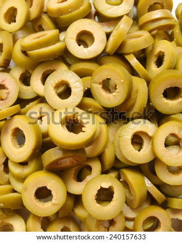 Small pile of sliced green olives isolated on background  - stock photo