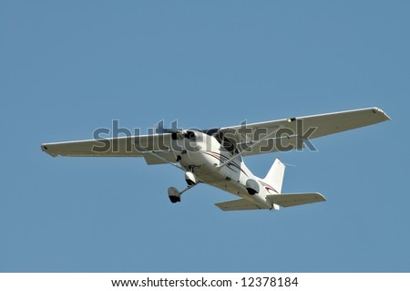 Small plane coming in for a landing against a clear sky - stock photo