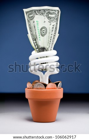 Small plant pot with a fluorescent light bulb a dollar and few dimes and pennies with a blue background - stock photo