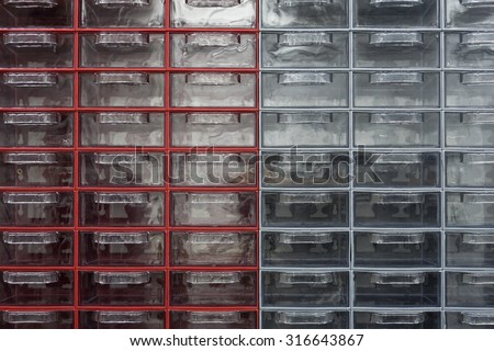 Small plastic transparent, empty drawers in red and gray carriers. - stock photo