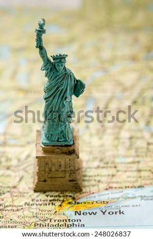 Small plastic version of the statue of liberty standing on the map near New York city, shallow DOF, focus on the head of statue. - stock photo