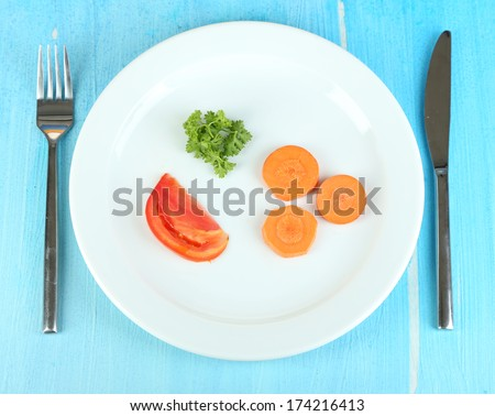 Small portion of food on big plate on wooden table close-up - stock photo