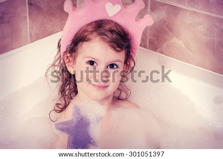 Small pretty girl is taking a bath and  with a foam - stock photo