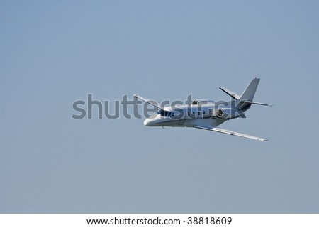 Small private jet landing or taking off with background of blue sky - stock photo