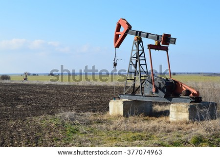 Small Pump Jack in agricultural field - stock photo