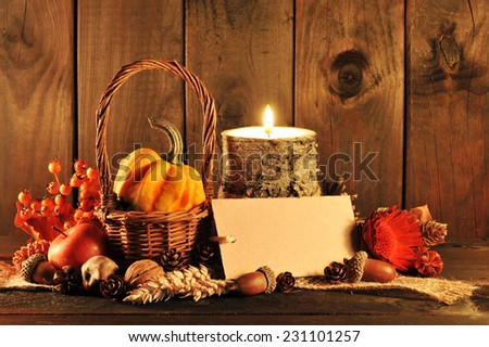 small pumpkin in basket on old weathered wooden floor in candlelight with copyspace - stock photo