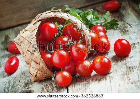 Small red cherry tomatoes spill out of a wicker basket on an old wooden table in rustic style, selective focus - stock photo