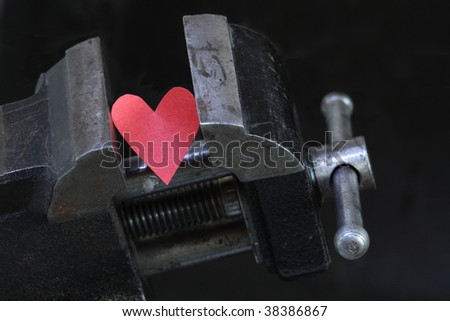 Small red paper heart under pressure with old vise grip on dark background - stock photo