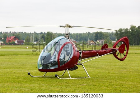 Small red private helicopter on grass on a background an overcast sky - stock photo