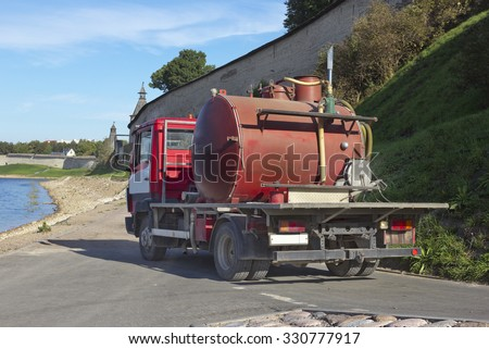 Small red sewage truck on the river bank - stock photo