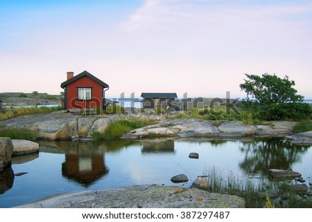 Small red wooden hut on a rocky skerry in the outer archipelago of Stockholm, Sweden. Grass in front and reflections in a small pond of water in front of the house. - stock photo