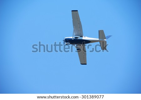 small retro airplane, clear blue sky in background - stock photo