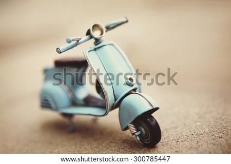Small retro scooter toy, toned sepia - stock photo
