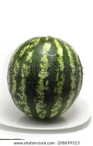 small ripe watermelon on a white plate - stock photo