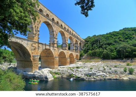 Small river and leisure boats under the Pont du Gard near Nimes, France - stock photo