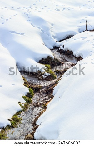 Small river flowing between two hills covered by white snow in winter time. - stock photo
