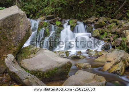 Small river in the deep forest turns into charming waterfall - stock photo