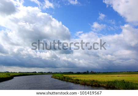 Small river in the netherland (friesland), against a partial clouded sky - stock photo