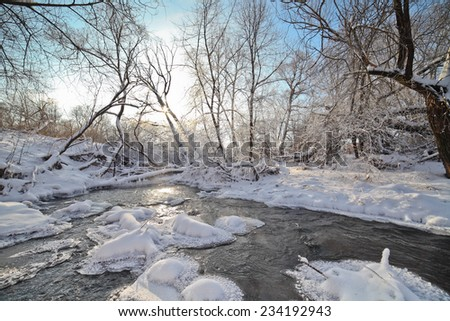 Small river in winter sunny day, with sunbeams through branches trees.   - stock photo