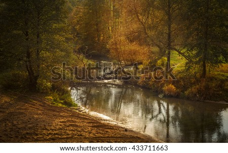 small river running through the autumn landscape - stock photo