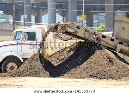 Small rock crusher and conveyor recycling construction salvage into usable aggregate - stock photo