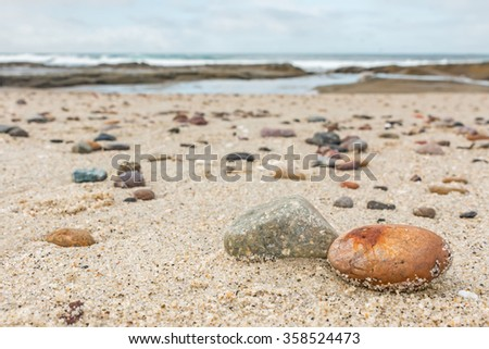 Small rocks scattered on beach sand close up.Shallow depth of field.Selective focus on foreground rocks.Blurred background of multicolor stones of different shapes and sizes,ocean waves,overcast sky   - stock photo