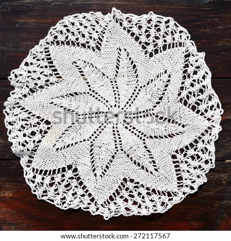 Small round crocheted tablecloth, handmade - stock photo