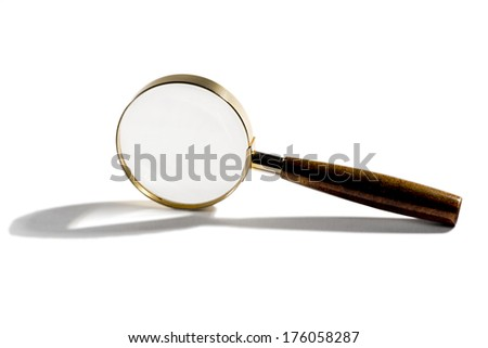 Small round handheld magnifying glass displayed on edge on a white background with a shadow conceptual of investigation, examination and research - stock photo