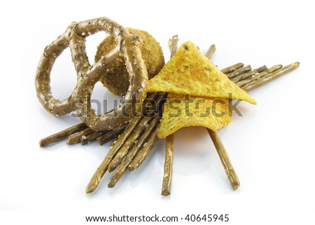 Small round scotch egg with salty pretzels and nachos on a reflective white background - stock photo