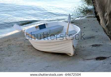 Small rowboat anchored at shore, in St. Petersburg, Florida - stock photo