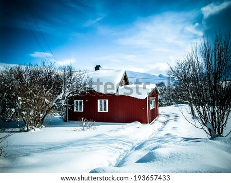 Small rural house in winter scenery. - stock photo