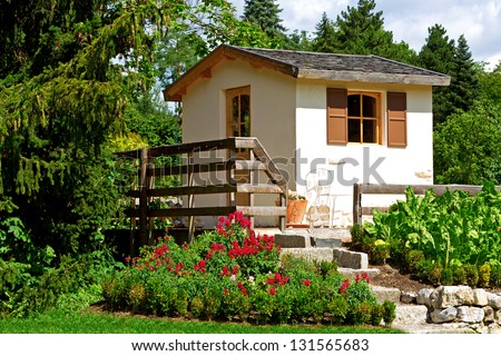 Small rustic cottage and garden - stock photo