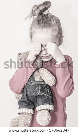 Small sad caucasian blond child girl crying while hugging teddy bear on a white background. Unhappy childhood concept. - stock photo