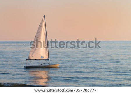 small sailboat in the water small sailboat in the water next to the beach next to the beach in a summer sunset ready to sailing with the last breeze of the day - stock photo