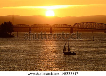 Small sailboat tacking back into port on the Columbia River near Portland Oregon at sunset with Interstate 5 bridge in background - stock photo