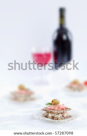 Small sandwich on white table top with bottle of wine on the background - stock photo