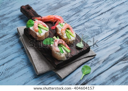 Small sandwiches bruschetta with ricotta cheese, shrimp, green onions, salad on a wooden surface - stock photo