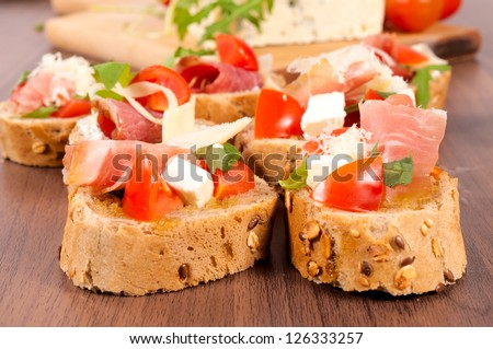 Small sandwiches on the wooden table - stock photo