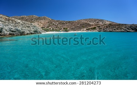 Small sandy beach with transparent waters and a small anchored boat, in Donousa island, Cyclades, Greece  - stock photo