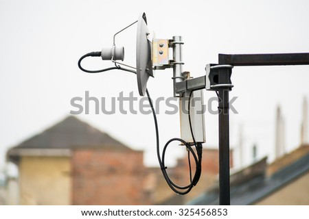Small satellite dish telecommunications receiver device on rooftop on city - stock photo