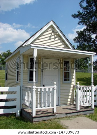 small scale yellow house with picket fence - stock photo