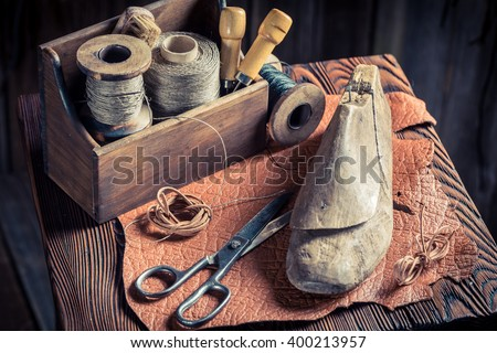Small shoemaker workplace with tools, leather and shoes - stock photo