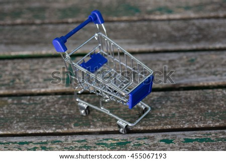small shopping cart, on a wooden table - stock photo