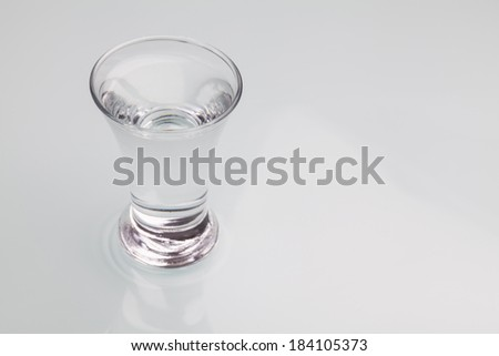 Small shot glass filled with alcohol isolated on gray background. Close-up studio photography  - stock photo